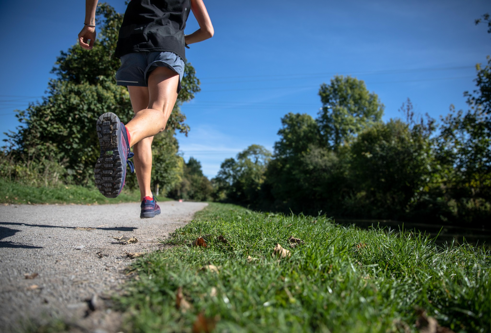 Photo of a woman running on a paved trail. Photo by Stage 7 Photography on Unsplash